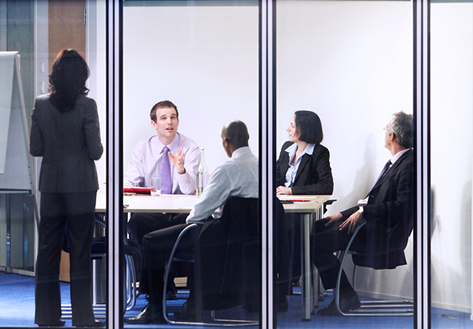 Business people sitting around a table talking while one person is standing up